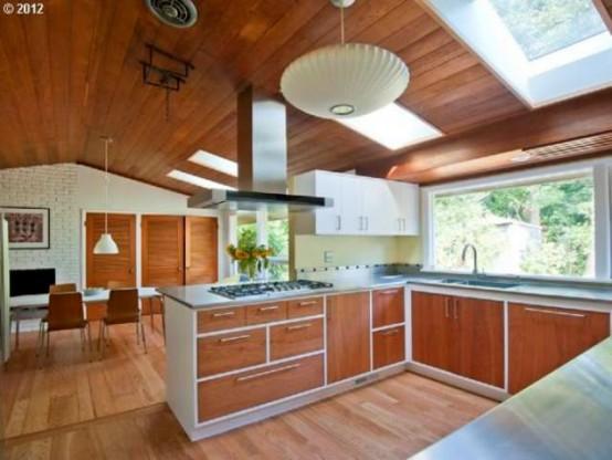 una luminosa cucina moderna della metà del secolo con armadi in legno, ripiani bianchi, lucernari e alzatina per finestre