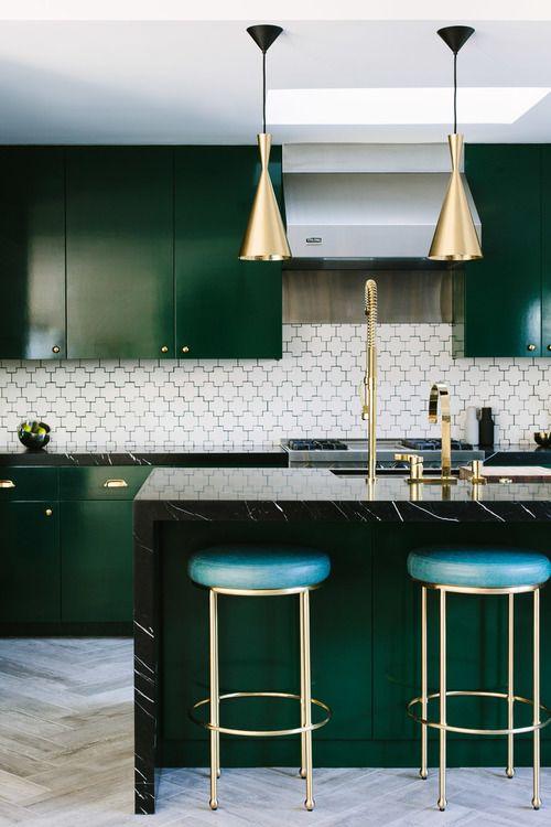 un'elegante cucina verde scuro con lampade a sospensione in ottone, sgabelli in pelle e ottone e alzatina in mosaico