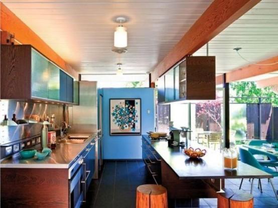 una cucina moderna della metà del secolo con armadi riccamente colorati, una grande isola cucina con uno spazio per mangiare e le tomaie sopra