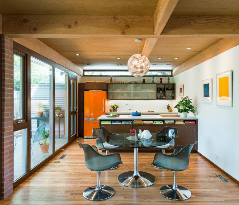 una cucina moderna della metà del secolo con una grande isola cucina in legno, un frigorifero arancione, una zona pranzo con comode sedie (Architectural Workshop)