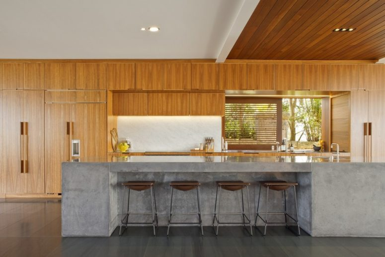 una ricca cucina in legno colorato con un'isola cucina in cemento e sgabelli in pelle (Richard Cole Architecture)