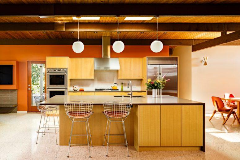 una cucina gialla con un'isola cucina a cascata con un piano di lavoro scuro, sedie in metallo e lampade a sospensione (architettura risa boyer)
