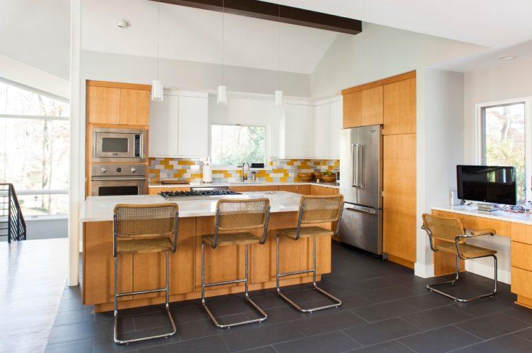 una cucina moderna della metà del secolo giallo chiaro con tocchi di sgabelli bianchi e filo metallico (Alair Homes Decatur)