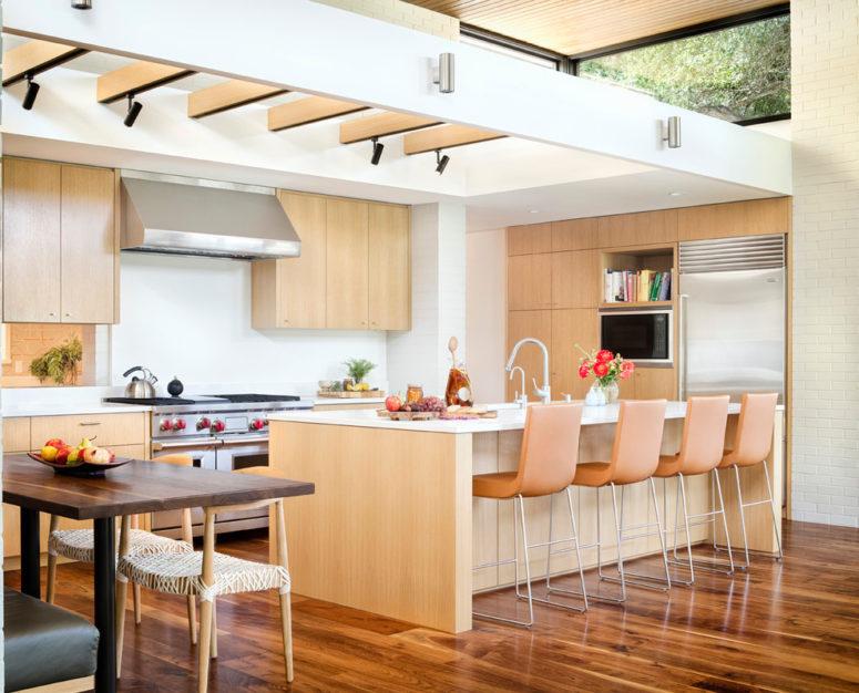 una cucina moderna della metà del secolo dai colori chiari con superfici bianche, sgabelli arancioni e molta luce (Allison Burke Interior Design)