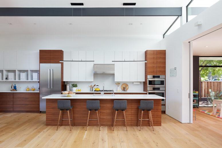 una cucina moderna della metà del secolo ricca e bianca con sedie nere e una grande isola cucina (Klopf Architecture)