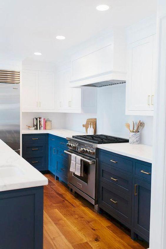 una cucina moderna della metà del secolo blu e bianca audace con ripiani bianchi e una cucina in metallo