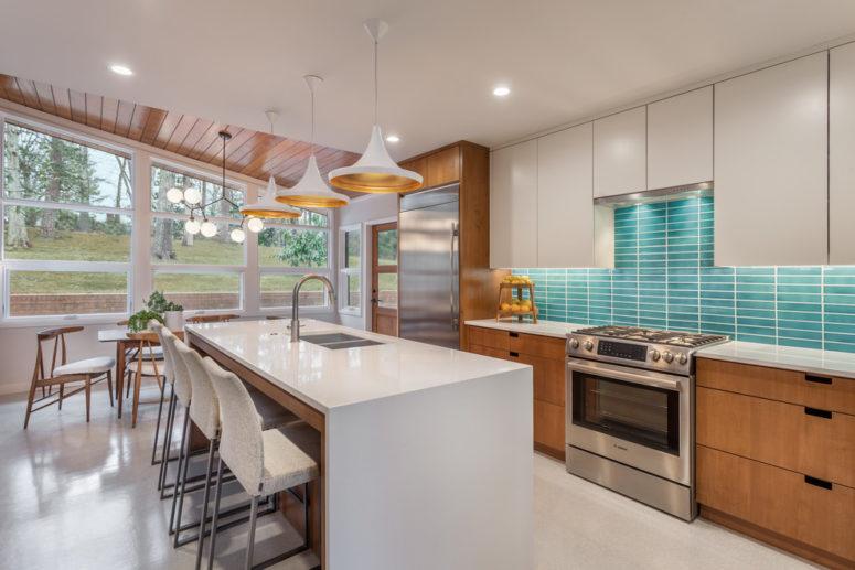 una cucina moderna della metà del secolo bianca e macchiata con un'isola della cucina bianca e un backsplash in piastrelle turchesi (CarsonSpeer Builders)