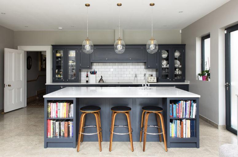 una cucina moderna grigia della metà del secolo con armadi in grafite, una grande isola cucina con un piano di lavoro bianco e lampade a sospensione (The Shaker Kitchen Company)