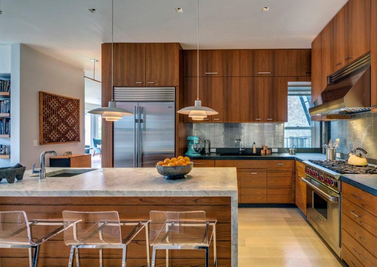una cucina moderna della metà del secolo ricca di colori con una grande isola cucina con un piano di lavoro in pietra e lampade a sospensione (sopra la costruzione)