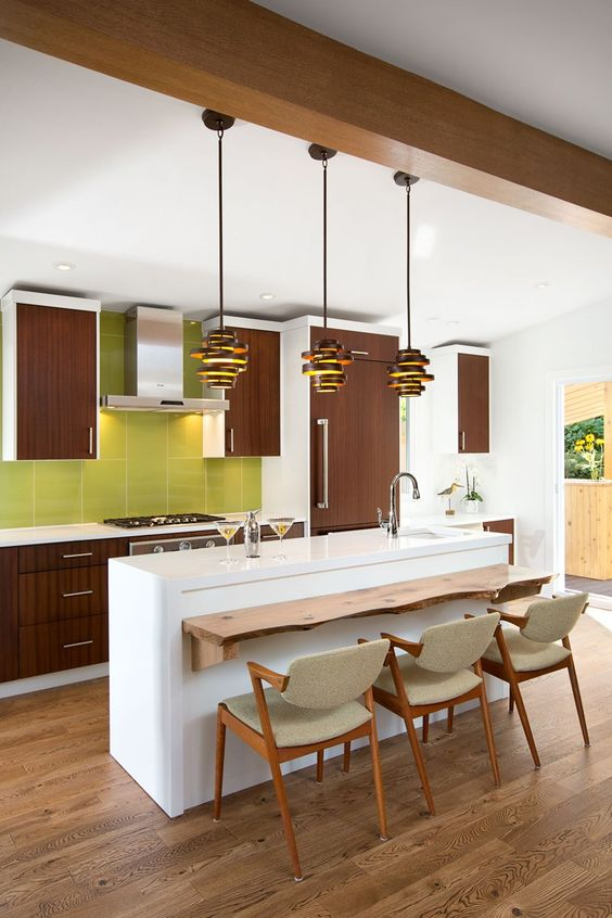 una cucina ispirata agli anni '60 con armadi marroni, un'isola cucina bianca e un alzatina in piastrelle verdi