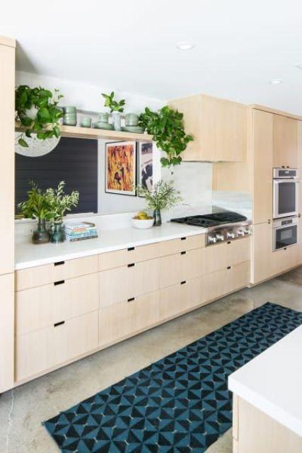 una cucina moderna della metà del secolo di colore chiaro in compensato, un tappeto a mosaico e molto verde