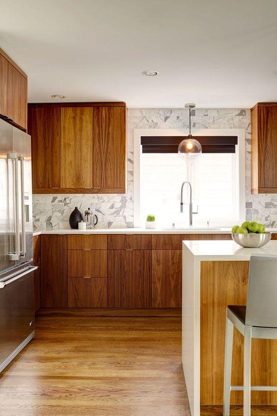 un contemporaneo incontra la cucina moderna della metà del secolo con un alzatina in piastrelle di marmo, lampade a sospensione e un'isola cucina con piano a cascata
