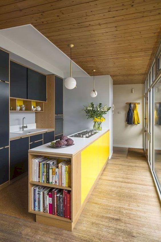 una cucina moderna colorata della metà del secolo con armadi blu scuro, un'isola da cucina gialla e lampade a sfera