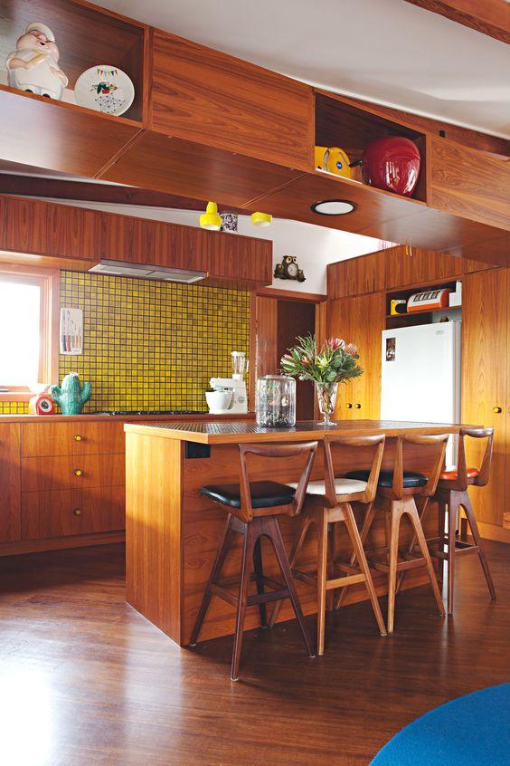 una luminosa cucina moderna della metà del secolo con armadi ricchi di tinte, un backsplash in piastrelle gialle e alti sgabelli in legno con schienali