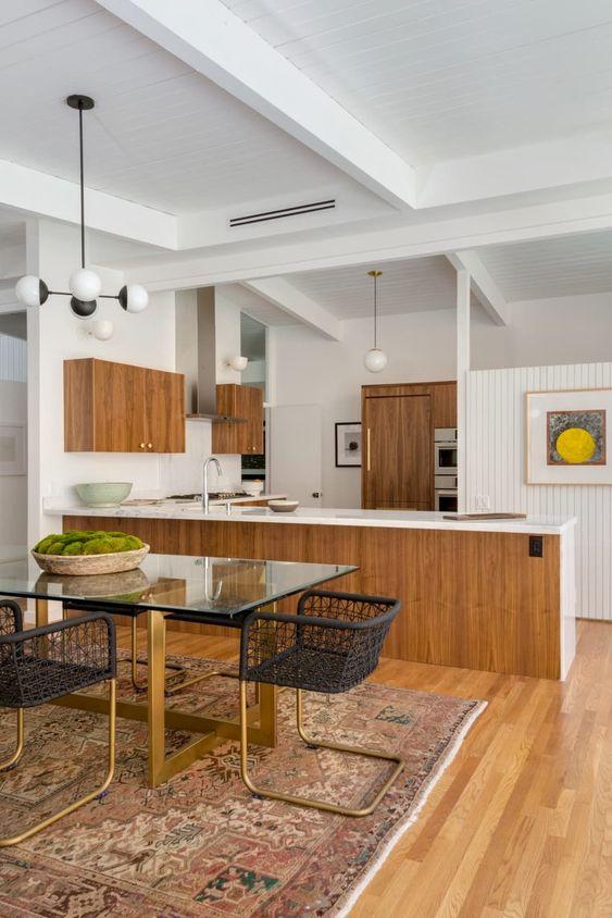 una grande cucina moderna della metà del secolo con armadi in legno, alzatine e top bianchi