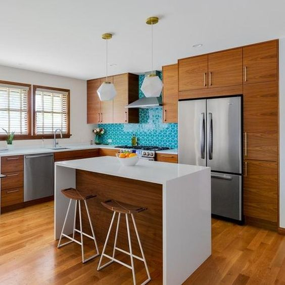 un'accogliente ma piccola cucina moderna della metà del secolo con armadi riccamente colorati, un backsplash in piastrelle turchesi, lampade a sospensione e un'isola da cucina