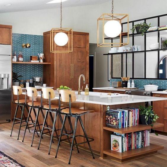 una cucina moderna della metà del secolo con armadi riccamente colorati e un'isola della cucina, un backsplash in piastrelle turchesi e lampade a sospensione geometriche