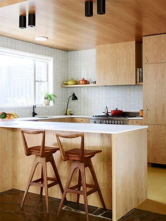 una cucina moderna della metà del secolo di colore chiaro con ripiani bianchi e pareti piastrellate e sgabelli in legno