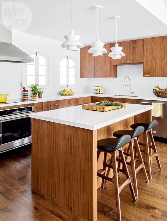 una cucina moderna della metà del secolo piena di luce con armadi riccamente colorati, ripiani bianchi, lampade a sospensione scultoree bianche