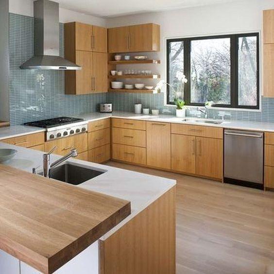 una cucina in legno di colore chiaro con ripiani bianchi, alzatina in piastrelle blu ed elettrodomestici in metallo