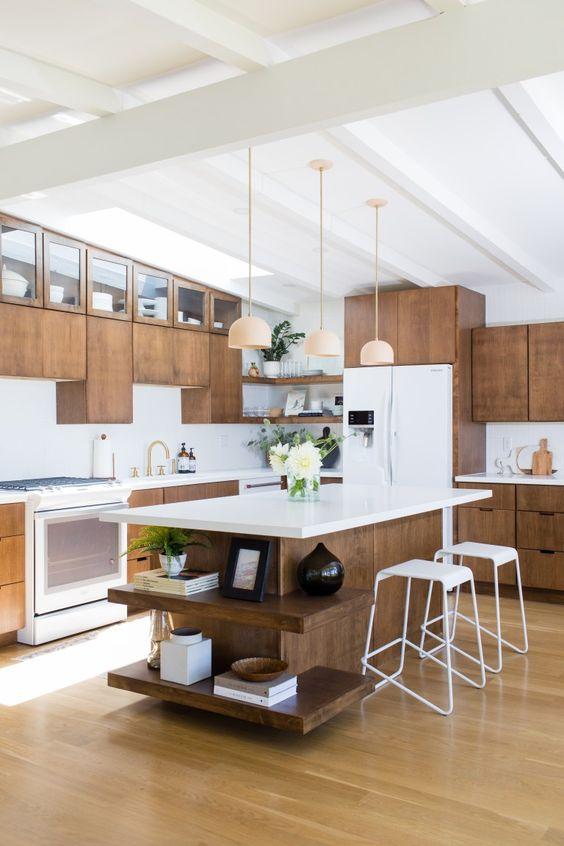 una cucina moderna della metà del secolo con armadi in legno, ripiani bianchi, lampade a sospensione e sgabelli bianchi
