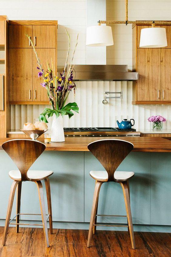 un'accogliente cucina moderna della metà del secolo con armadi di colore chiaro con maniglie metalliche, sgabelli in compensato, un'isola da cucina blu e un piano di lavoro in legno