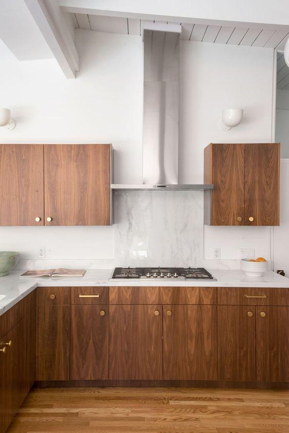 una cucina moderna della metà del secolo in legno tinto ricco con ripiani bianchi, alzatina in pietra bianca