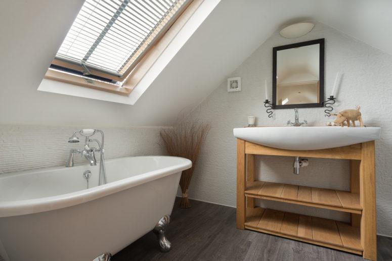 un moderno bagno in mansarda con un lavabo in legno, una vasca da bagno con piedini, un lavandino e una finestra con cieca (Colin Cadle Photography)