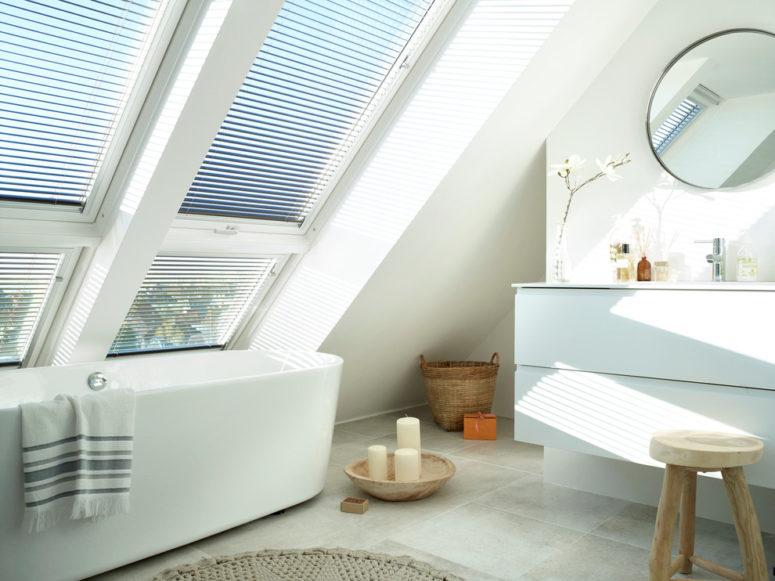 un moderno bagno in mansarda con grandi finestre, una vasca ovale, un lavabo con specchio rotondo, uno sgabello in legno (VELUX)