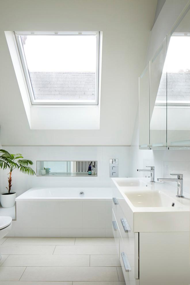 un ampio bagno mansarda in colori neutri e azzurro con un grande lucernario e un doppio lavabo (Dyer Grimes Architecture)