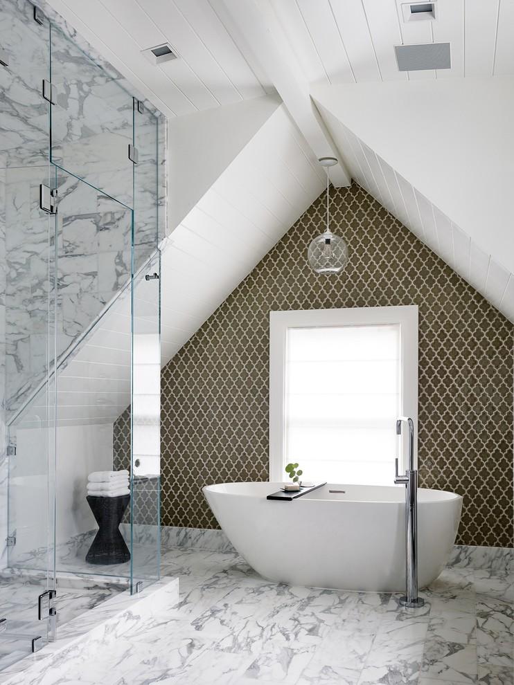un elegante bagno in mansarda con piastrelle di marmo, una vasca ovale, un accattivante muro di piastrelle (Art of Construction Inc)