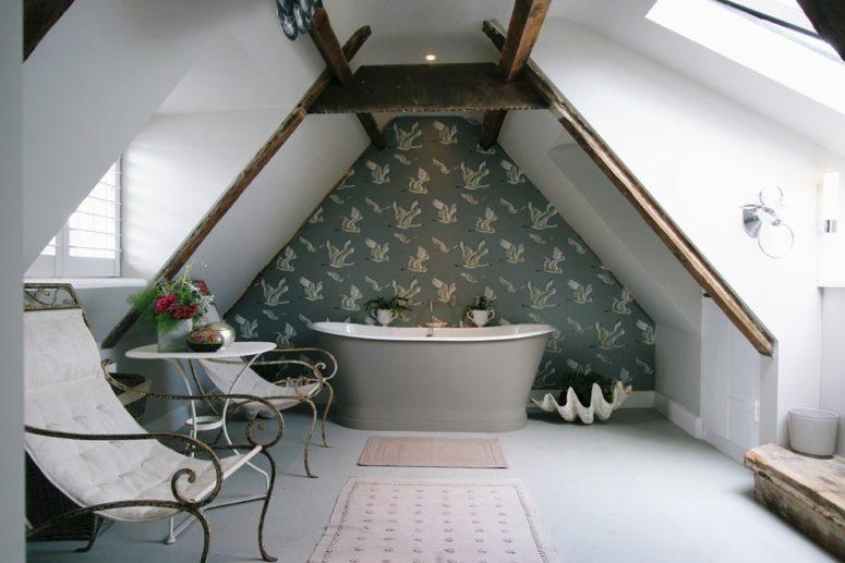 un elegante bagno in mansarda con un muro di carta da parati, una vasca da bagno grigia, sedie eleganti e fiori in vaso (Aston Matthews)