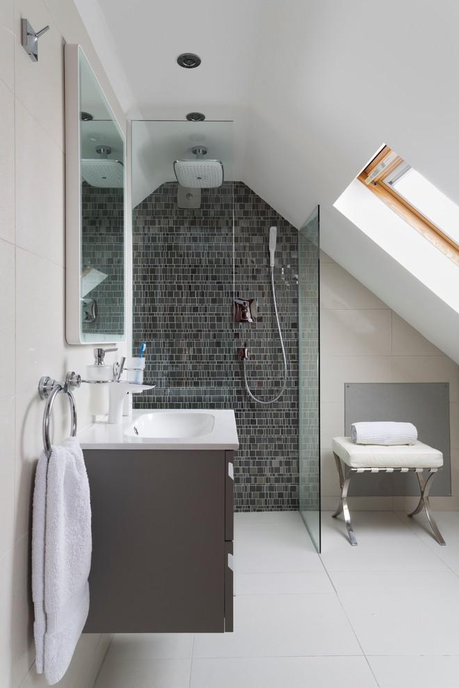 un moderno bagno mansardato con un muro di piastrelle grigie nella doccia, un mobile lavabo grigio e un piccolo sgabello (Ripples Bournemouth)