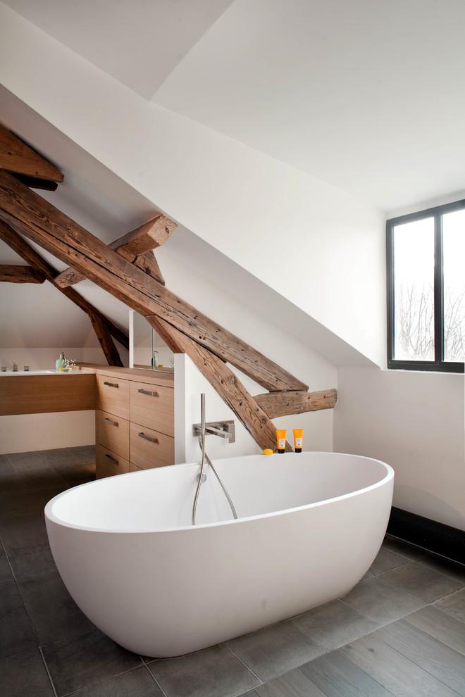 un bagno contemporaneo incontra il rustico con travi in legno, una vasca ovale e armadi bianchi