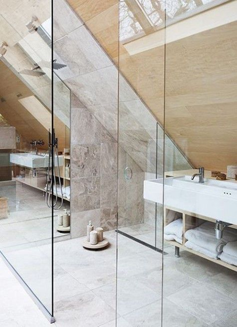 un bagno mansardato in piastrelle di marmo e legno con spazio doccia, molte candele e lucernari
