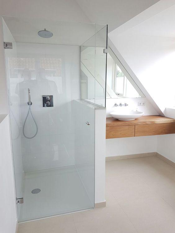 un bagno in mansarda minimalista con una vanità galleggiante in legno e una doccia bianca