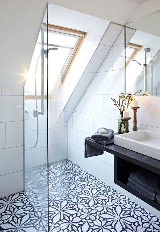 un bagno in mansarda bianco e nero con piastrelle a mosaico, uno spazio doccia con lucernari, un lavabo sospeso