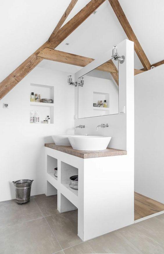 un moderno bagno in mansarda bianco con travi in legno e controsoffitti più vani portaoggetti incorporati