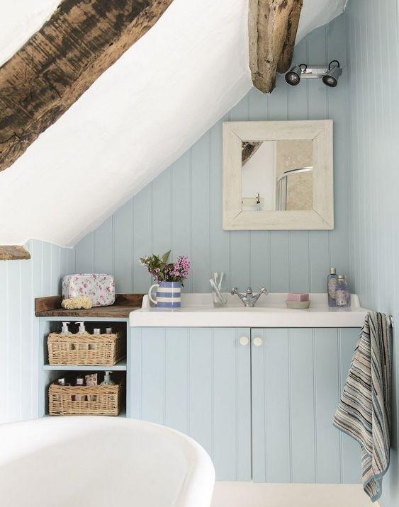 un piccolo bagno in mansarda azzurro polvere con travi in legno, cestini portaoggetti e vasca free-standing