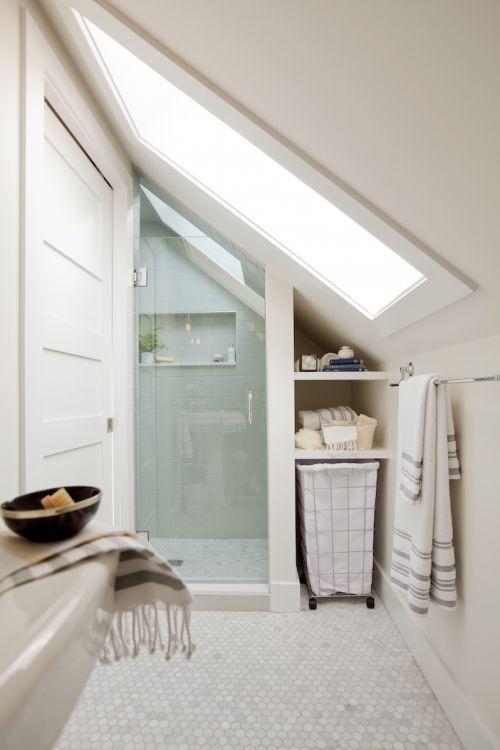 un bagno in mansarda neutro con spazio doccia realizzato con piastrelle aqua, piastrelle in marmo penny sul pavimento e un grande lucernario