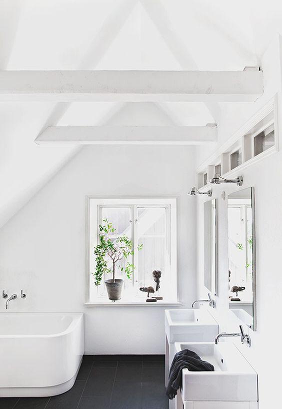 un bagno mansardato puro hwite con un pavimento di piastrelle nere, due lavandini e una vasca da bagno curva