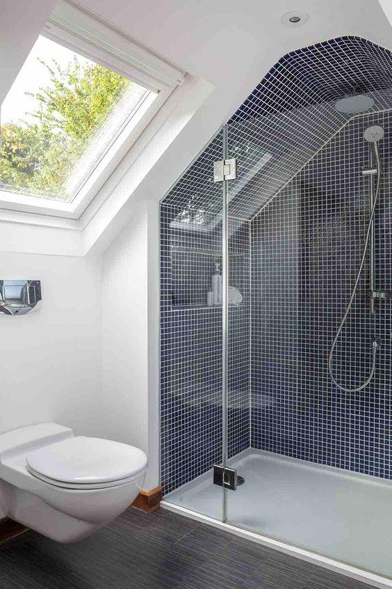 un minuscolo bagno in mansarda con piastrelle blu scuro e stucco bianco, un pavimento grigio e un lucernario