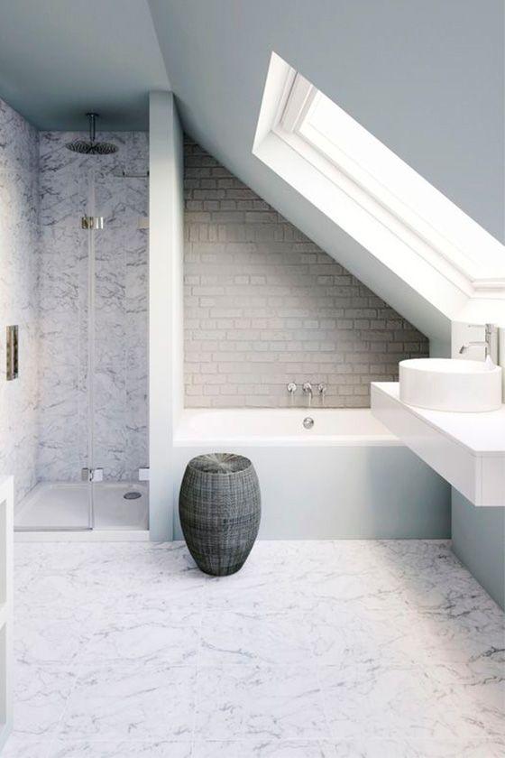 un bagno in mansarda neutro con piastrelle di marmo, finto mattone, un cesto per la conservazione e un lucernario e una vanità galleggiante