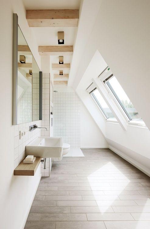 un bagno mansardato arioso e minimalista con uno spazio doccia e una vanità galleggiante più alcuni tocchi di legno