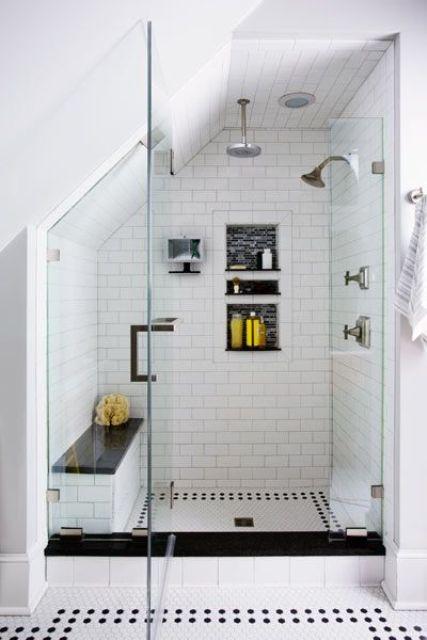 uno spazio doccia mansarda bianco e nero con tessere di mosaico, una panca e nicchie per lo stoccaggio