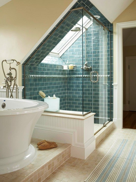 un bagno in mansarda con vano doccia rivestito di piastrelle blu e una raffinata vasca e un tappeto a righe