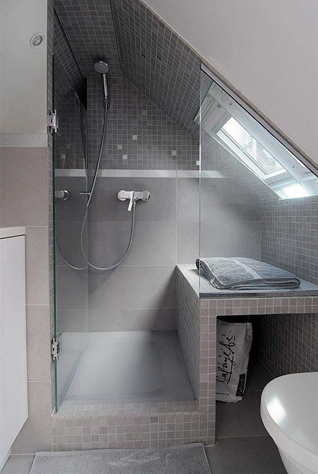 un piccolo bagno in mansarda neutro con lucernario nella doccia, piastrelle grigie e tortora