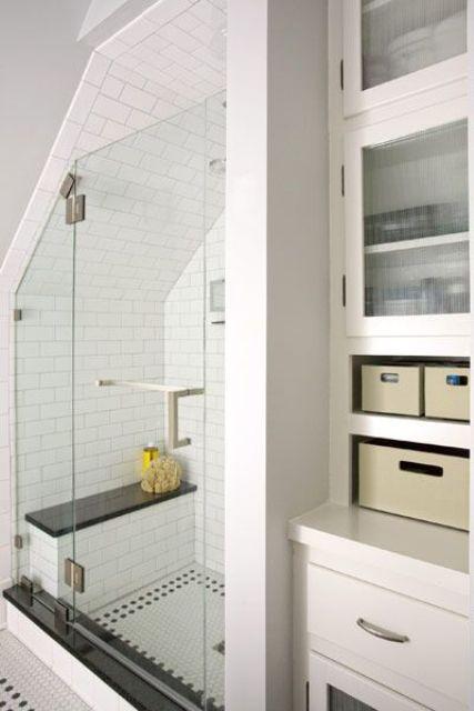 un bagno neutro con cassetti e contenitori chiusi, metropolitana e piastrelle penny nello spazio doccia