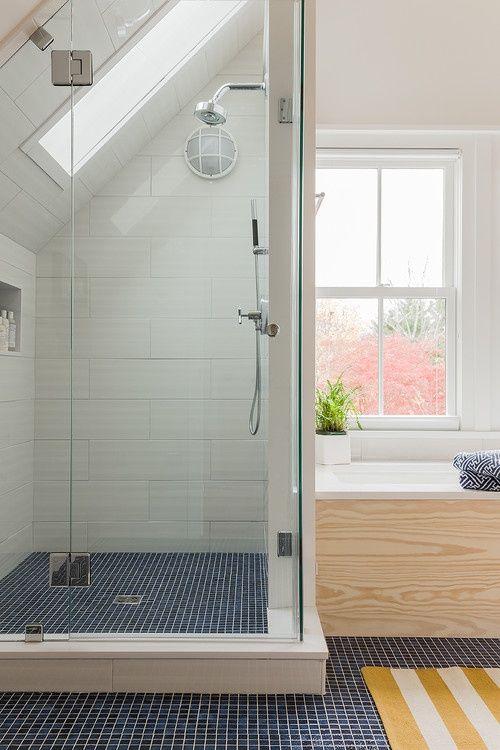 uno spazio doccia con piastrelle navy, un grande vano portaoggetti sotto il davanzale della finestra
