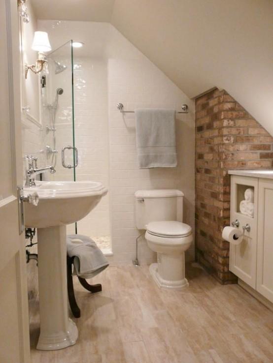 un piccolo bagno in mansarda con un muro di mattoni, piastrelle bianche, un lavabo da terra e un lavabo sospeso